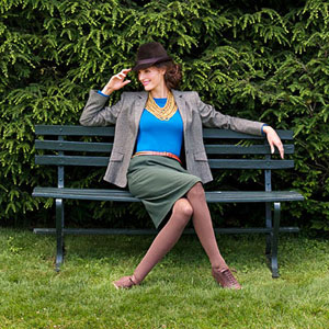 Model on bench in tweed blazer and skirt
