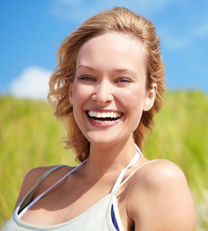 Close-up of happy blonde woman outside