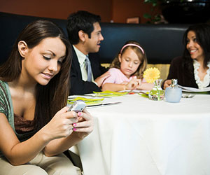 teen on her cell phone at dinner table