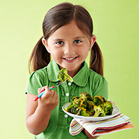 Girl eating broccoli