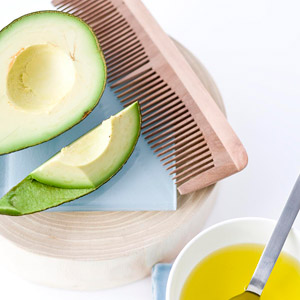 Avocado, oil, and comb for hair treatment