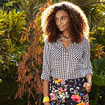 Woman in gingham blouse and black flower pants