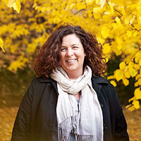 Erin Puariea standing in front of yellow leaves
