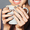Woman with grey nails holding coffee mug