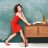 Tina Fey in red dress holding onto desk