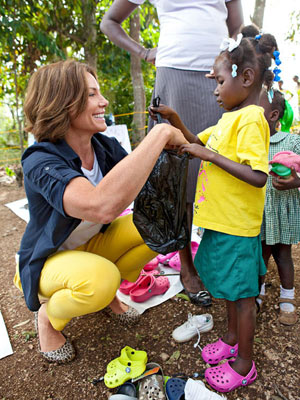 LuAnn De Lesseps holding bag with child in Haiti
