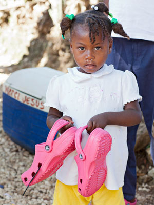 Little Haitian girl holding pink Crocs