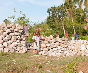 Children standing by log pile in Haiti