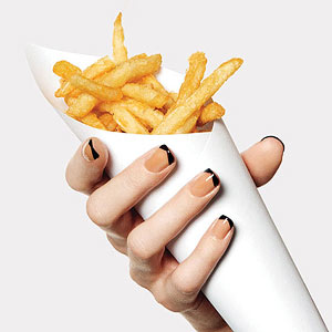 Hands with black and peach manicure holding French fries