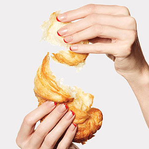 Hands with red French manicure holding croissant