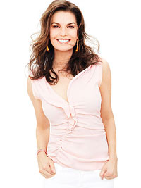 Sela Ward in pink ruffle top and white jeans