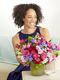 Woman in purple dress with LHJ floral bouquet