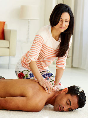 Woman straddling man lying down and massaging his lower back
