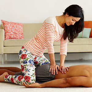 Woman straddling and giving lower back massage to man lying down (face not shown)
