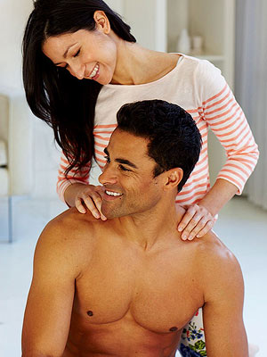 Woman massaging man who is sitting down