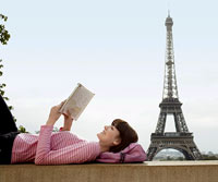 Woman reading by Eiffel Tower