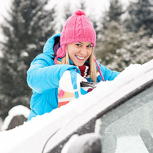 Woman cleaning snow off car