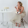 Woman sitting down in white room eating cake
