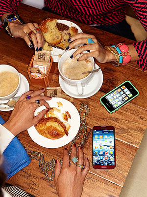 Two women sitting with coffee, pastries, and cell phones