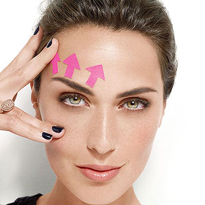 Model with younger eye makeup and pink arrows above eyebrow