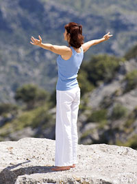 Woman on cliff with arms open