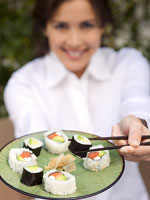 Woman holding a plate of sushi