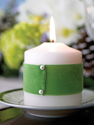 green ribbon pinned with peals on white candle