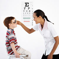 boy getting eyes checked by doctor