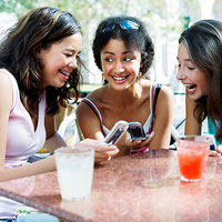Girls using cell phones and laughing