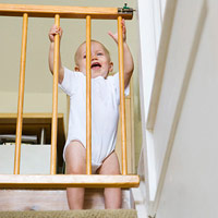 baby holding onto gate on stairs