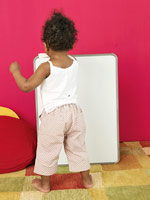 Toddler writing on a dry-erase board