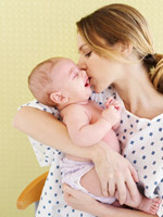 woman kissing newborn
