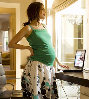 pregnant woman standing above computer