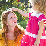 girl putting crown on mothers head