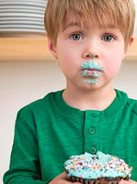 boy with cupcake frosting on face