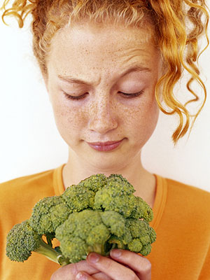 girl looking at head of broccoli