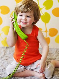 toddler holding green telephone