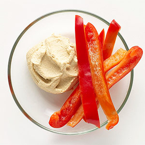 Red pepper slices and bowl of hummus