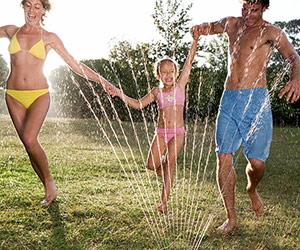 playing in lawn sprinkler