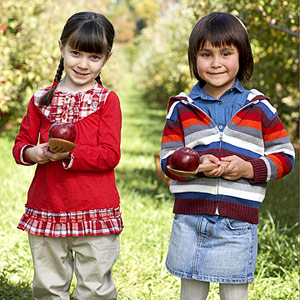 Kids holding spoons with apples