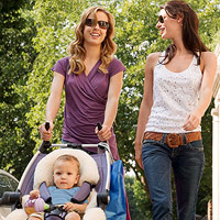 women talking while taking baby for a walk