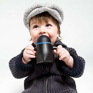 toddler holding sippy cup and smiling