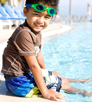 Boy sitting on edge of pool