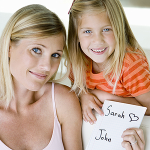 pregnant mother and young daughter holding a list of baby names