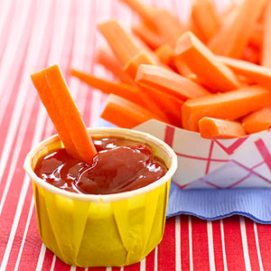 Dipping carrots in ketchup