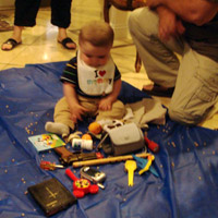 Baby Haroot chooses objects in his Armenian ceremony
