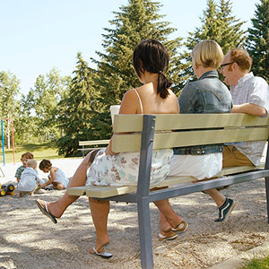 parents at the sandbox watching children play