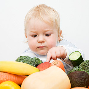 baby looking at vegetables