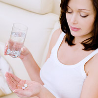 woman holding glass of water and prenatal vitamin