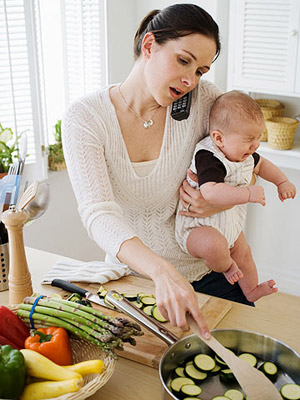 woman in the kitchen cooking holding crying baby